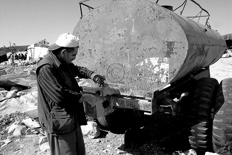 Jihad Nawajeh, 42, checks the water tank in the Palestinian village of Susyah, in the West Bank. The water crisis has increased in the West Bank in the last months due the Israeli restrictions on water. Amnesty International has accused Israel of denying Palestinians adequate access to water while allowing Jewish settlers in the occupied West Bank almost unlimited supplies. Photo by Quique Kierszenbaum
