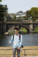 A man uses a selfie-stick to take a photo at the Imperial Palace in Tokyo.