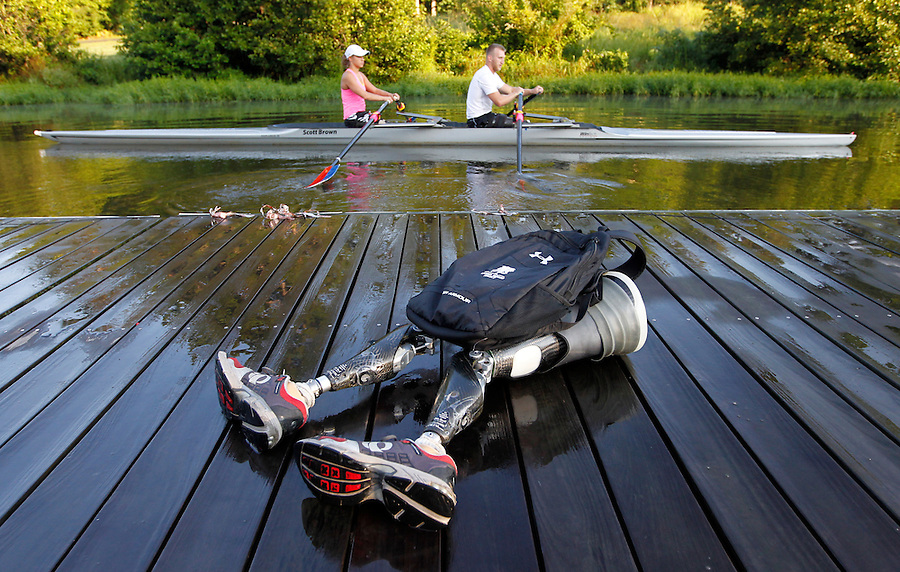 Leaving his bionic legs behind former Marine sergeant Rob Jones, right, begins a training workout with partner Oksana Masters Wednesday July, 25, 2012 on the Rivanna River in Charlottesville, VA. Former Marine sergeant Jones, who lost both legs during an IED explosion in Afghanistan, will compete with Masters as rowers at the 2012 Paralympics in London, England. Rowing will make its appearance at the London Paralympic Games for only the second time, after its introduction at the Beijing 2008 Games. Photo/Andrew Shurtleff