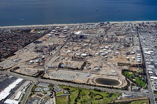 View of the Chevron - El Segundo Oil Refinery from the air looking west. Today the refinery covers approximately 1,000 acres, has more than 1,100 miles of pipelines, and is capable of refining over 270 thousand barrels of crude oil per day (Chevron.com).