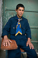 A boy, who is responsible for security, sits at the main door of the Parwan Agriculture College.