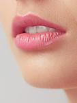 Closeup of young woman lips, slightly open mouth and pink lipstick