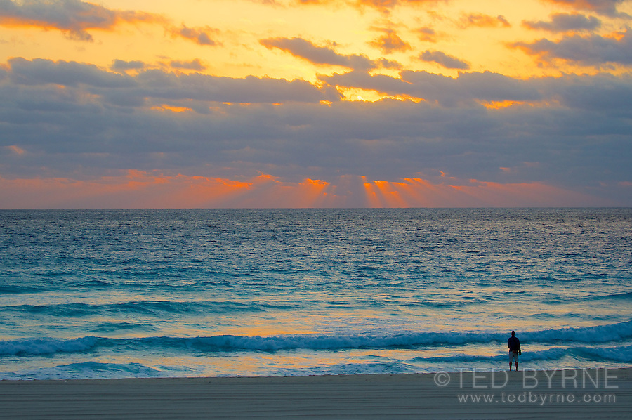 Man standing on a beach watching morning   sunrays break through the clouds (landscape)