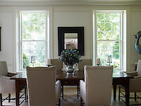 A 17th century English oak table in the breakfast room is surrounded by a set of high-backed linen-upholstered armchairs