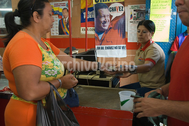 Consumidores venezolanos compran comida en Mercal del centro de Caracas, mercado auspiciado por el gobierno venezolano. Muchas personas compran bienes debido al gran flujo de gastos de gobierno, cr?ditos bancarios privados y el miedo a la inflaci?n.  Uno de los hechos econ?micos m?s importantes, en estos a?os, ha sido el control monetario impuesto por la administraci?n de Ch?vez, colocando el precio del d?lar a 2150 bol?vares mientras que en el mercado negro se vende de 3500 a 4200 bol?vares, y limitando el cupo de consumo en gastos electr?nicos y de viajes. Caracas, 6-03-07 (Ram?n Lepage/Orinoquiaphoto) <-> Venenezuelan consumers buying food at the government sponsored Mercal food chain store in downtown Caracas, March 06, 2007. Many people are buying goods due to the large cash flow from government spending, enticing private bank loans and also fears of inflation in the economy. The Chavez adminitration implemented more than 3 years ago a currency control, setting the the price of 2150 bolivares per dollar while the black market price is about 3500 to 4200 bolivares. Venezuelans are allowed to spend during the year up to  $ 5000 for travel and $3000 for internet shopping. (Ram?n Lepage/Orinoquiaphoto)