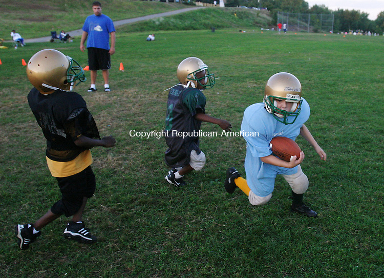 WATERBURY, CT 8/28/07- 082807BZ06- Jacob Colon, 9, of Waterbury, right, runs the ball under pressure from Ezra Alves, 8, of Waterbury, center, as Rontay Williams, 7, of Waterbury, left, comes in to block during practice with his Waterbury Knights Mighty Mites football team at the Laurel Hill Complex behind Wilby High School in Waterbury Tuesday night.   Head coach Steve Ayres watches the action from the backfield.   The team is part of the American Youth Football Mid Conn. league. The Knights is comprised of about 300 players and cheerleaders and practices 5 nights a week until school starts.  During the school year they practice three nights a week.<br /> Jamison C. Bazinet Republican-American