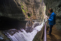 Tourist at Skocjan Caves, Slovenia, looking at the Waterfall at the bottom of the 'Big Valley' (Velika Dolina), Karst Region of Slovenia, Europe