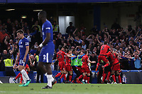 Huddersfield Town players celebrate their opening goal scored by Laurent Depoitre as Chelsea's Cesar Azpilicueta and Antonio Rudiger dejectedly walk back to the centre-circle during Chelsea vs Huddersfield Town, Premier League Football at Stamford Bridge on 9th May 2018