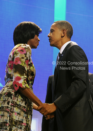 United States First Lady Michelle Obama (L) and US President Barack Obama (R) kiss at the Clinton Global Initiative (CGI) in New York, New York, USA, 23 September 2010. President Obama joined sixty-four current and former heads of state in attending the sixth annual meeting of the CGI.  The commitment of CGI members has improved the lives of more than 220 million people in 170 countries, according to President Bill Clinton.  The 2010 meeting features a session on 'Peace and Beyond in the Middle East'.  .Credit: Michael Reynolds - Pool via CNP