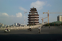 Huizhou, Guangdong province, China - Commuters pass the ancient Hejiang Tower, October 2014.