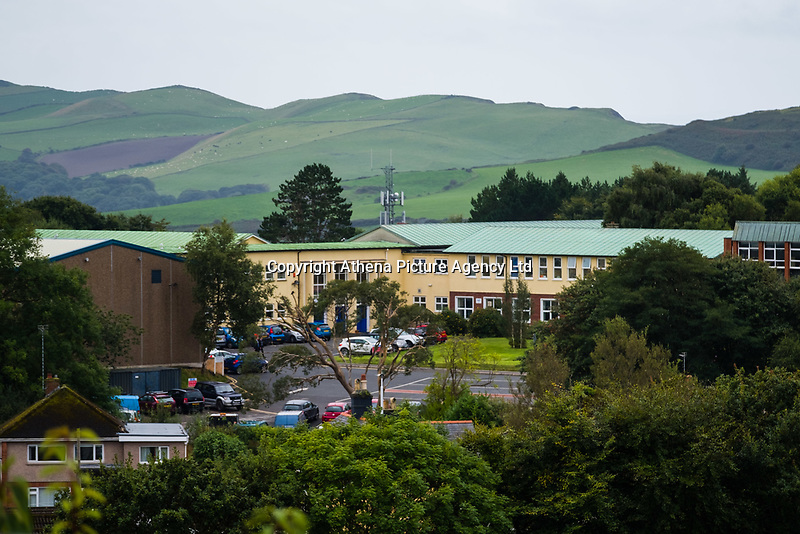 """COPY BY TOM BEDFORD<br /> Pictured: Ysgol Penglais School in Aberystwyth, Wales, UK<br /> Re: More than 400 pupils at a comprehensive school in Aberystwyth were given detention on their first day back for breaking school uniform rules.<br /> The uniform was changed at Ysgol Penglais over the summer, following a consultation.<br /> But a number of parents have complained to the school and some 250 have signed a petition saying the punished pupils were """"treated unfairly"""".<br /> Ceredigion council said a large number of pupils were kept in at break times.<br /> The new uniform was brought in for the start of the new academic year, with the old navy blue pullover and white polo shirt replaced by a grey v-neck jumper, white shirt and a tie. Sixth formers have a similar outfit.<br /> It is compulsory for all pupils in years 7 and 12 to wear the new uniform, with other students being given the rest of the year to buy it.<br /> This was outlined in correspondence sent to all parents over the summer months, which also stipulated what trousers, skirts and shoes would be deemed acceptable.<br /> But the petition said the new rules were not clear enough and that the pupils should not have been punished for their parents' mistakes.<br /> It also said a warning should have been given before the detention."""
