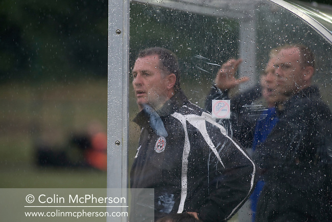 The backroom staff of Irish club Bohemians watching the action through the rain at Park Hall Stadium, Oswestry during their team's Champions League 2nd qualifying round 2nd leg game away to The New Saints. Despite leading 1-0 from the first leg, the Dublin club went out following their 4-0 defeat by the Welsh champions. The match was the first-ever Champions League match in the UK played on an artificial pitch and was staged at the Welsh Premier League's ground which was located over the border in England.