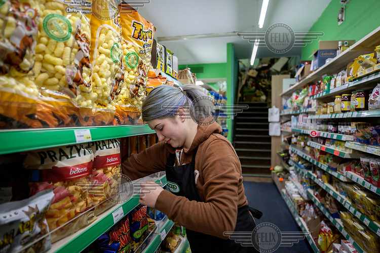 A woman stocks the shelves of Misiek, a Polish shop which supplies a large community of people who emigrated within the EU to work in Scotland.