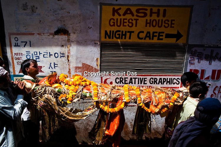 A dead body is carried along the alleys to the burning ghat in the ancient city of Varanasi in Uttar Pradesh, India. Photograph: Sanjit Das/Panos