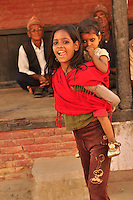 Young girl carrying her baby sister in the traditional baby-carrier. Street photo, Kathmandu, Nepal