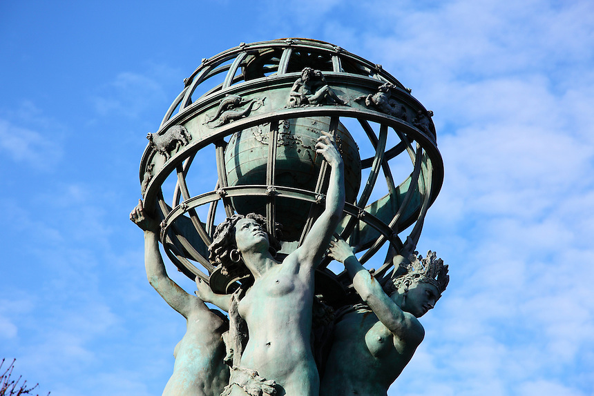The Fountain of the Observatory (Fontaine de l'Observatoire) near the Luxembourg garden in Paris: the top of the metal statue with the globe against the sky. Digitally Improved Photo.