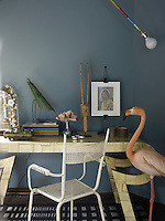 A stuffed flamingo stands beside a vintage table at one end of the guest bedroom