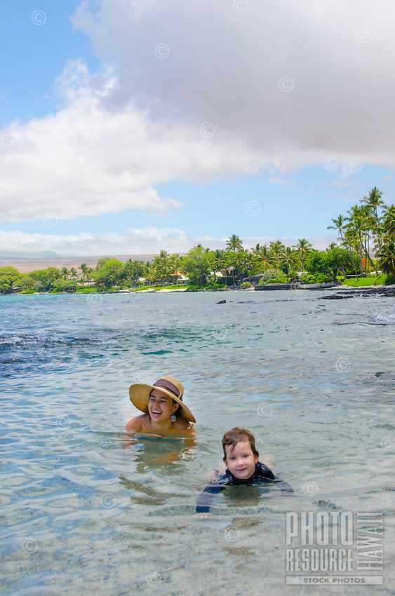 A local mother and daughter enjoy their time in a tide pool at a beach in Puako, South Kohala, Hawai'i Island.