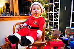 A young child, dressed in a Santa suit, sits for a Christmas portrait.