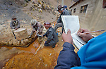 Carlos Rojas, a student assistant, takes notes as Freddy Llanos, a professor of mining engineering at Tomas Frias University, samples water quality outside the Kumurana Mine near Caiza D, Bolivia. The mine, which is closed, produces highly toxic acid runoff that negatively impacts the farms and lives of people living downstream. Llanos is working with an international coalition that is working with local miners and farmers to clean up the mine's runoff. Helping Llanos is Policarpio Montesinos, a local miner.