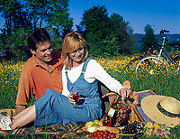 Paar beim Picknick in einer Blumenwiese, mit Fahrraedern im Hintergrund | couple having a picnic in a flower meadow, bycicles in background