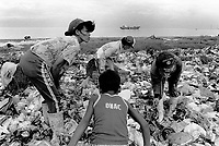 Philippines. Luzon Region. Manila. Tondo area. Smokey mountain is a rubbish dump. Life on a garbage heap. A group of scavengers on dumpsite. They collect various rubbish items in order to resell them as recycled products. Three women and a young boy. A merchant vessel is on the sea. © 1992 Didier Ruef ..