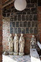Gothic statues are lined up in a dilapidated summer house