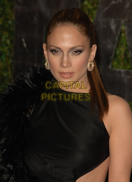 JENNIFER LOPEZ.The 2010 Vanity Fair Oscar Party held at The Sunset Tower Hotel in West Hollywood, California, USA..March 7th, 2010.oscars headshot portrait black silk satin cut out sides sleeveless feathers gold earrings  .CAP/RKE/DVS.©DVS/RockinExposures/Capital Pictures.