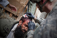 US Army Medic Sgt. Ester, Viper Company 126, 1st Platoon, treats Mohammed, a local driver from Korengal village who was shot in cross-fire at Restrepo Firebase in the restive Korengal Valley. Mohammed was driving on the road close to the firebase when he was stopped and searched by ANA (Afghan National Army) soldiers. AAF (Anti Afghan Forces) then opened fire at them and the Restrepo base. In the ensuing firefight a shot hit his head but did not penetrate the skull and it was unclear if the shot was from coalition or AAF shots. Restrepo, a remote outpost, is known as one of the most violent places in Afghanistan. Located in the Korengal Valley it comes under fire on a daily basis from Anti-Afghan Forces in the local villages and mountains.