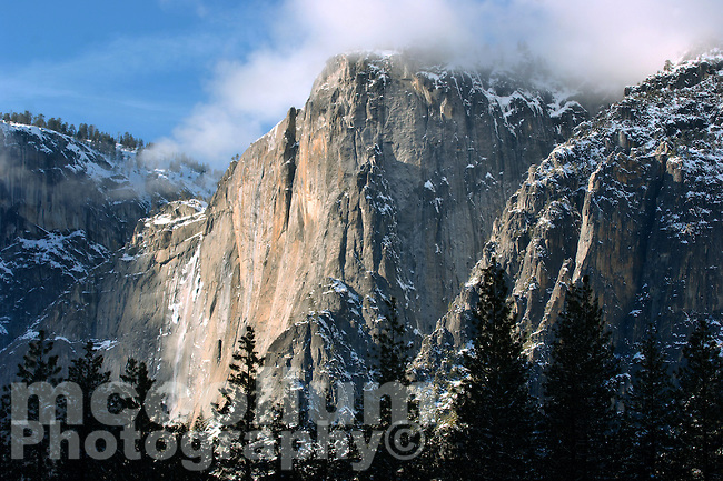 Magestic Yosemite Valley's cliffs, near Yosemite Falls,  during a winter sunset, with mist and alpine glow.