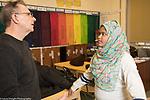 Education High School male teacher talking to female student wearing head scarf