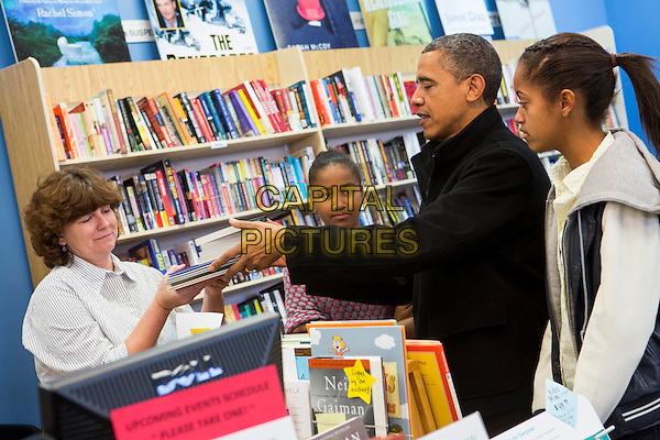 United States President Barack Obama, center, and daughters Sasha, left, and Malia, right, shop in Arlington, Virginia on Small Business Saturday, .November 24th, 2012 .half length side profile black white pink jacket top father dad family hand arm.CAP/ADM/CNP/KT.©Kristoffer Tripplaar/CNP/AdMedia/Capital Pictures.