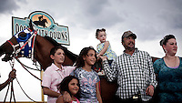 A Mexican family pose for a picture during a horse racing meeting at a track in Dodge City, Kansas. Horse racing is a popular past time for many of the Hoispanic community in the region.