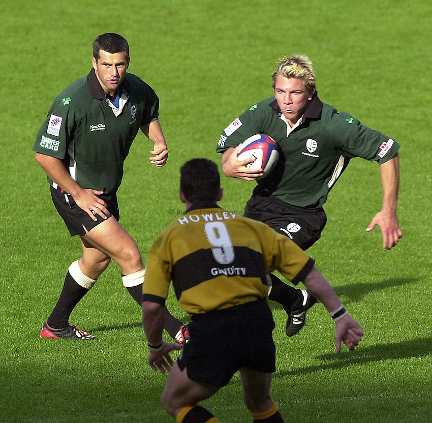 Photo Peter Spurrier.29/09/02   ZURICH PREMIERSHIP RUGBY.London Irish vs Wasps.Justin  Bishop with ball and Barry Everitt,  attacking Wasps defender Rob Howley