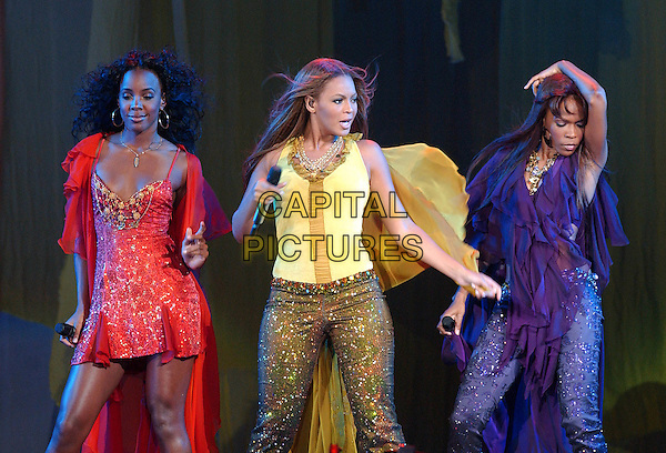 "KELLY ROWLAND, BEYONCE KNOWLES & MICHELLE WILLIAMS.Destiny's Child.""Destiny Fulfilled ...And Lovin It"" Tour.Mellon Arena.Pittsburgh, 20th July 2005.stage gig music half length half-length gold glitter trousers microphone yellow top red dress purple singing.www.capitalpictures.com.sales@capitalpictures.com.© Capital Pictures."