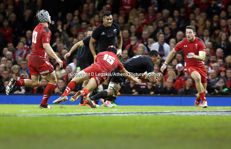 Pictured: Keven Mealamu of New Zealand (C) scores a try, Leigh Halfpenny of Wales (15) fails to stop him Saturday 22 November 2014<br /> Re: Dove Men Series 2014 rugby, Wales v New Zealand at the Millennium Stadium, Cardiff, south Wales, UK.