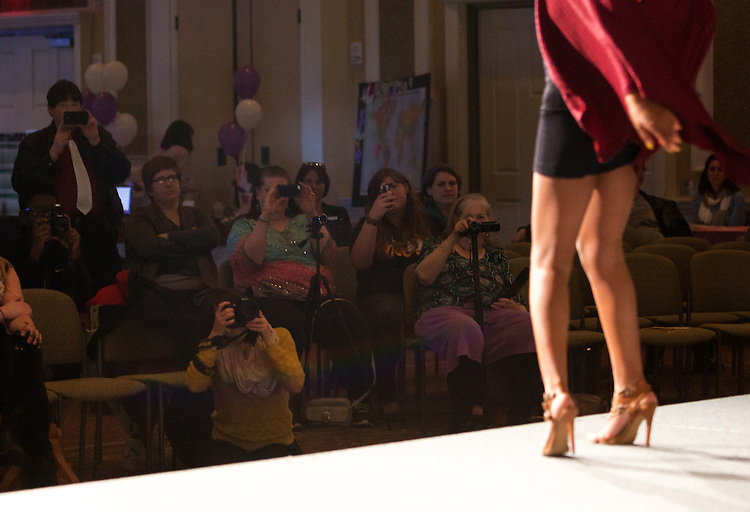 Audience members take pictures as a member of FACES Modeling Club participates in a fashion show during the Sixth Annual International Women's Day Festival, held in Baker Center Ballroom on March 16, 2014. The event, sponsored in part by the Ohio University Women's Center, educated audiences about women's progress, celebrated women's achievements, and included numerous performances by female members of the Athens and Ohio University community. International Women's Day itself fell on March 8, 2014. Photo by Lauren Pond