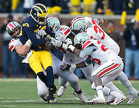 Ohio State Buckeyes defensive lineman Joey Bosa (97) (left), Ohio State Buckeyes defensive lineman Noah Spence (8), Ohio State Buckeyes linebacker Joshua Perry (37) and Ohio State Buckeyes cornerback Armani Reeves (26) bring down Michigan Wolverines quarterback Devin Gardner (98) during the fourth quarter of the NCAA football game at Michigan Stadium in Ann Arbor, Michigan on Saturday, November 30, 2013. (Columbus Dispatch photo by Jonathan Quilter)