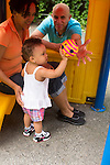 14 month old toddler girl outside at playground with parents