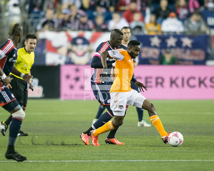 Houston Dynamo midfielder Warren Creavalle (5) controls the ball with New England Revolution midfielder Saer Sene (39) in pursuit.  The New England Revolution played to a 1-1 draw against the Houston Dynamo during a Major League Soccer (MLS) match at Gillette Stadium in Foxborough, MA on September 28, 2013.