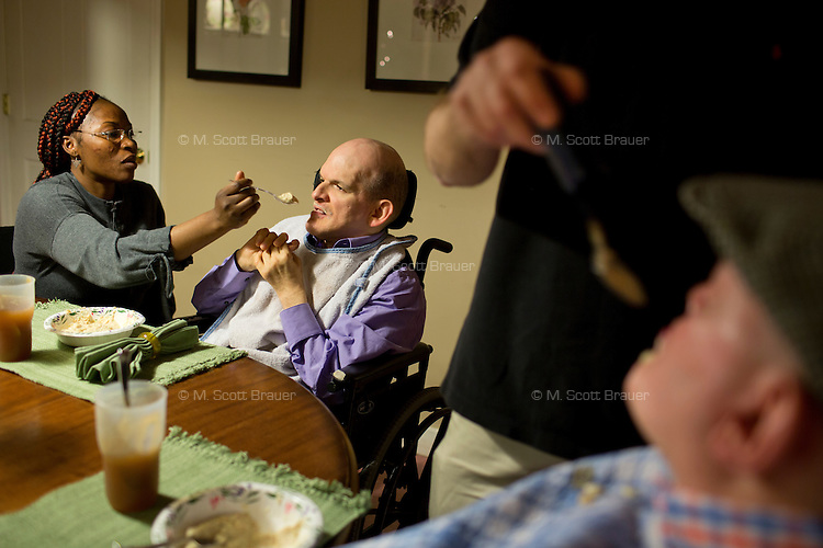 Caregiver Mariam Komate helps Frank Bandolfh, 56, (center) eat at a table for dinner as Kevin Calahane, LPN, feeds resident David Gilmore, 66, (right), at an assisted living home run by Northeast Residential Services in Bedford, Massachusetts, USA.  The residents previously lived at the Fernald Developmental Center in Waltham, Massachusetts, USA.