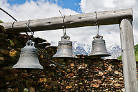 "Bells of the medieval Georgian Orthodox St George Church ""JGRag"" with mount Shkhara (5193m) behind, Ushguli, Upper Svaneti, Samegrelo-Zemo Svaneti, Mestia, Georgia. At 2,200 m (7217 ft) above sea level in the Caucasus mountains St George Church is one of  the highest in Europe. Mount Shkhara is the highest mountain in the Caucasus range and the highest in Europe."