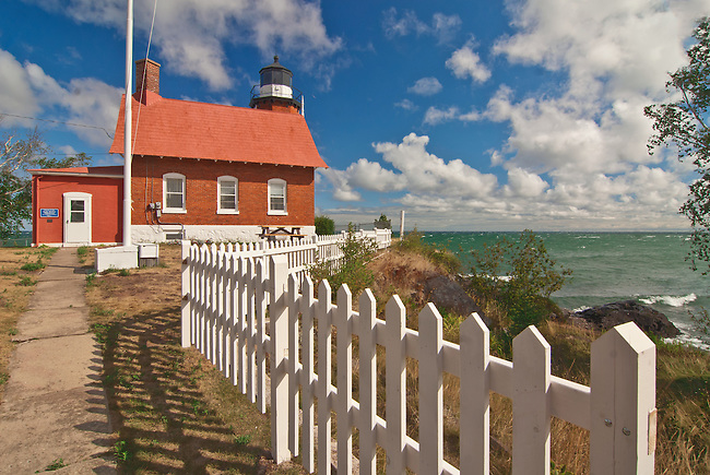 Eagle Harbor Lighthouse is framed by a white picket fence in Michigan's Upper Peninsula's Keweenaw Peninsula