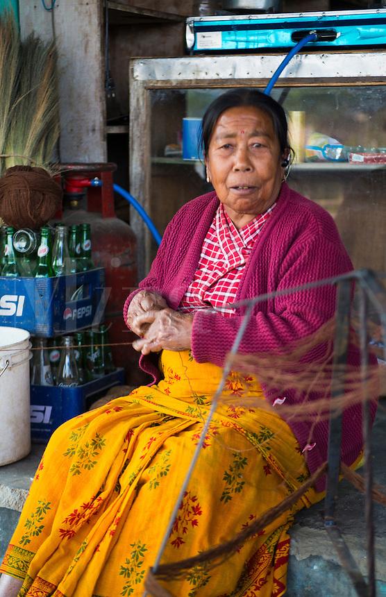 Kathmandu Nepal Nepali weaving woman posing and weaving threads for carpets in Nayapati, Eastern Kathmandu   42