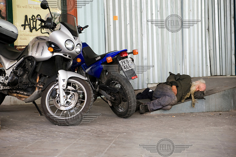 A homeless man sleeps next to motorcycles at the entrance of the abandoned ministry of Education and Religion in Mitropoleos street in central Athens.