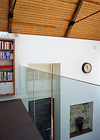 View over the glass wall of the mezzanine into the open-plan living space