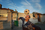 A man heads a soccer ball while playing football in the street in the largely Roma neighborhood of Gorno Ezerovo, part of the Bulgarian city of Burgas. Residents here don't self-identify much as Roma, because of the negative connotations associated with the word, so many refer to themselves as a Turkish-speaking minority.