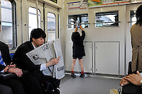 A boy taking a photo of the train driver in Tokyo, Japan.<br />19 Mar 2010