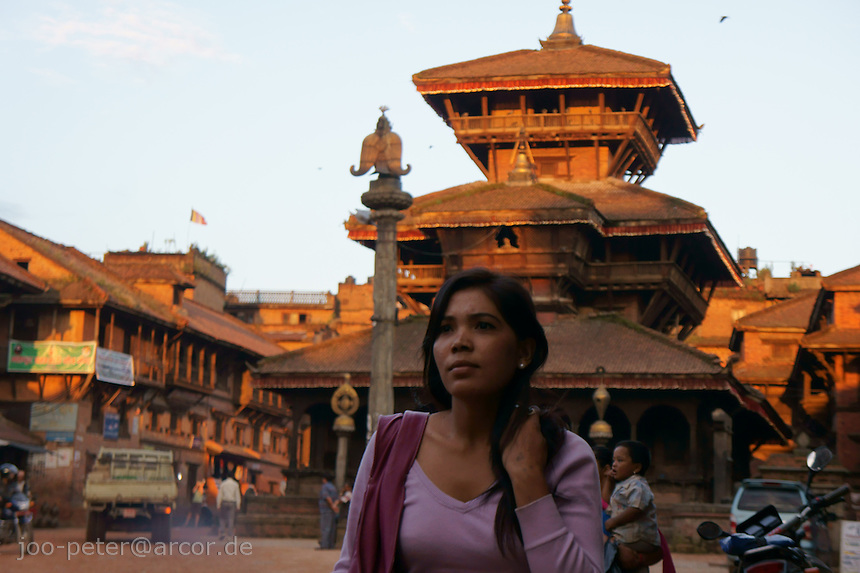 woman crossing Tachapol Square  in Bhaktapur,Nepal in warm sunset light.