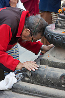 Bodhnath, Nepal.  Worshiper Prays at a Shrine at the Base of the Bodhnath Stupa, a Tibetan Buddhist Stupa.